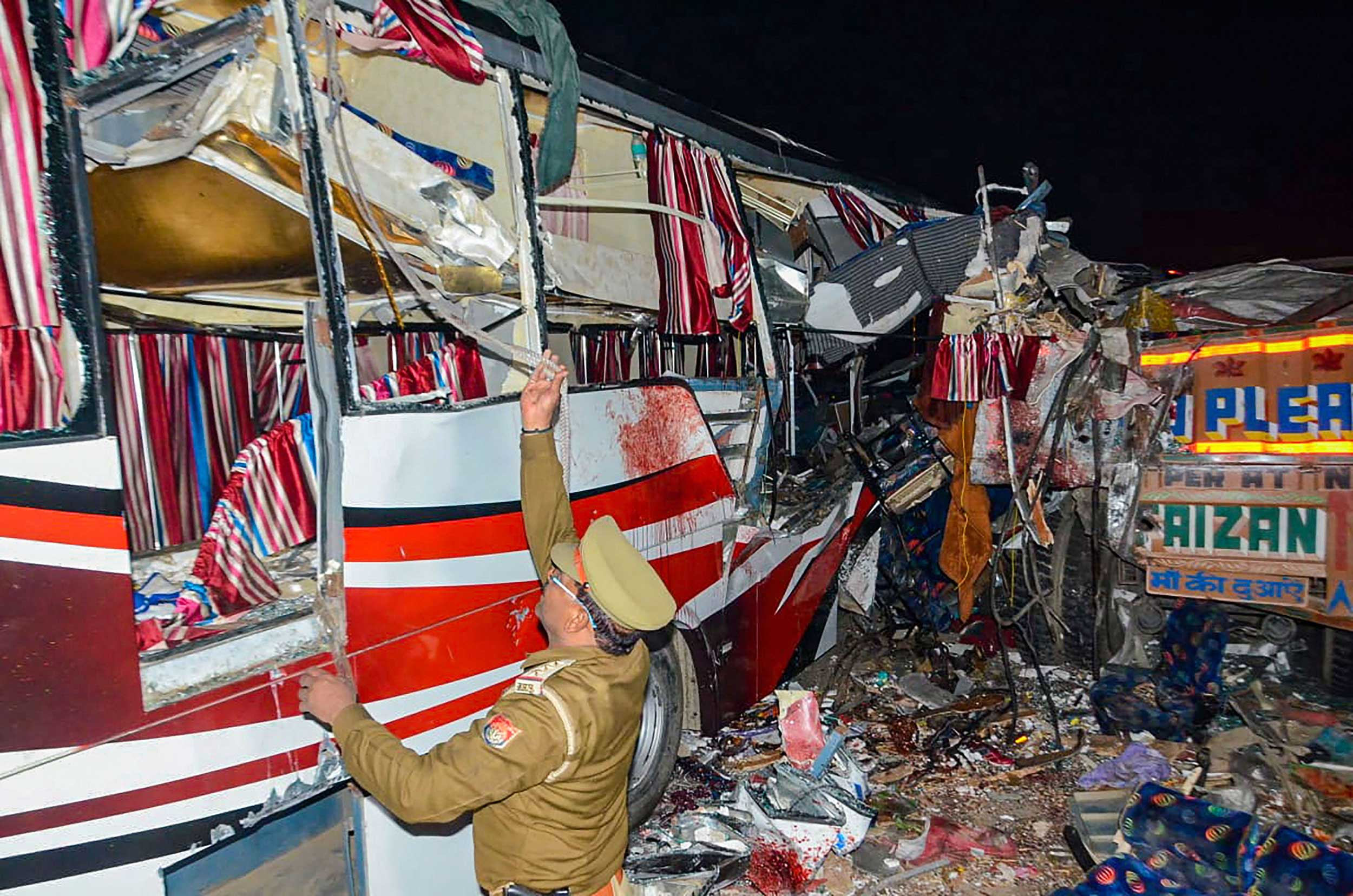 A policeman inspects the mangled private bus which collided with a truck on the Agra-Lucknow Expressway, in Firozabad, on Thursday.