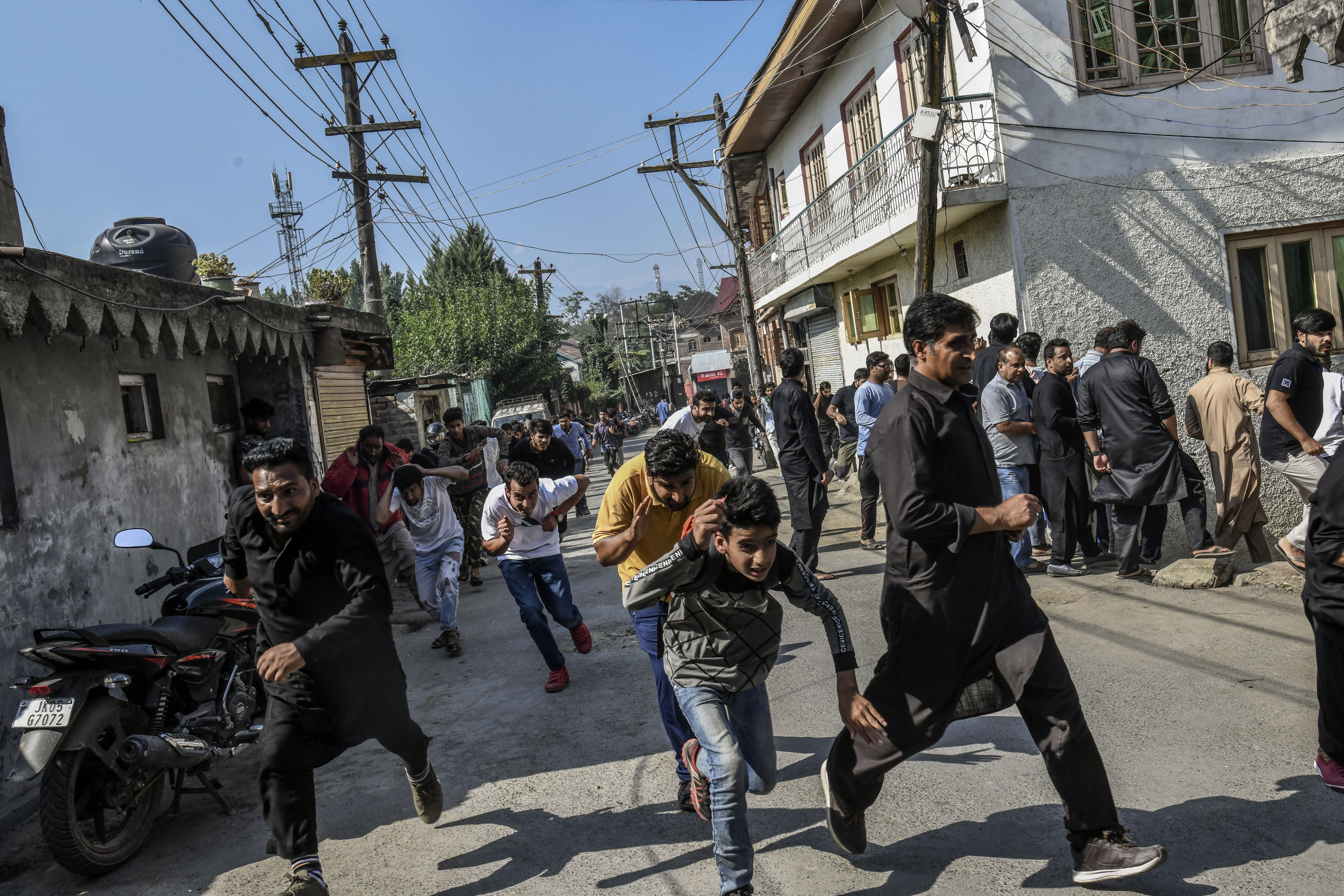 Residents run from security forces' tear gas and riot guns in Srinagar, India, September 7, 2019.