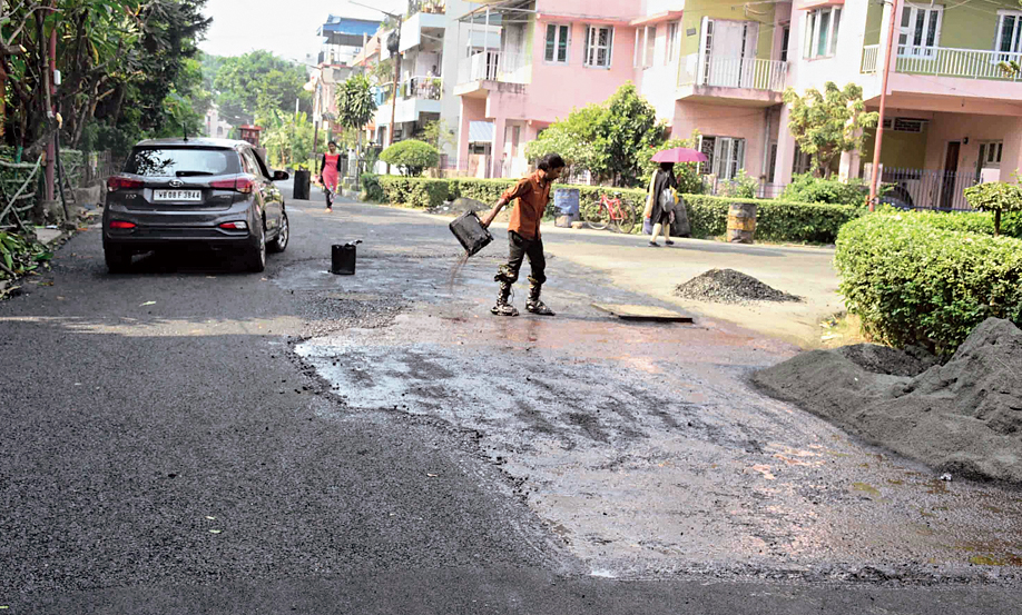 A worker pours molten bitumen on the road to do patchwork repairs in FE Block.