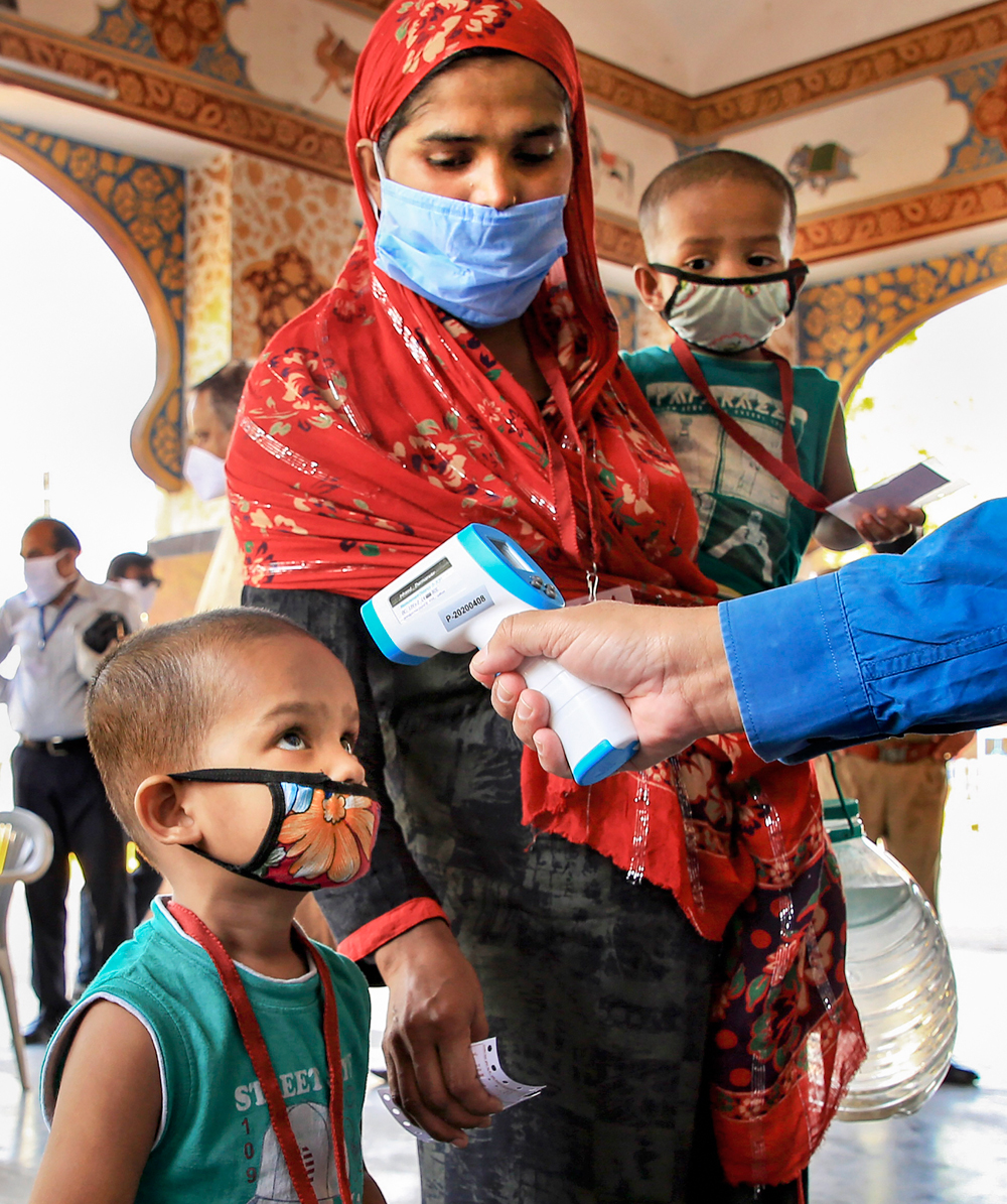 A medic checks temperature of a child as stranded people wait to board a special train for West Bengal to reach their native place, amid Covid-19 lockdown in Ajmer, Monday, May 4, 2020.