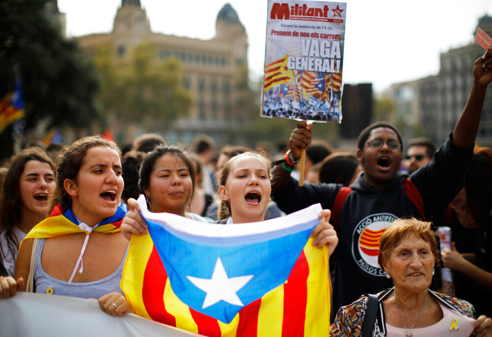People wearing yellow ribbons in support of jailed pro-independence politicians and carrying Estelada pro-independence flags protest in Barcelona, Spain on Monday, October 14, 2019.
