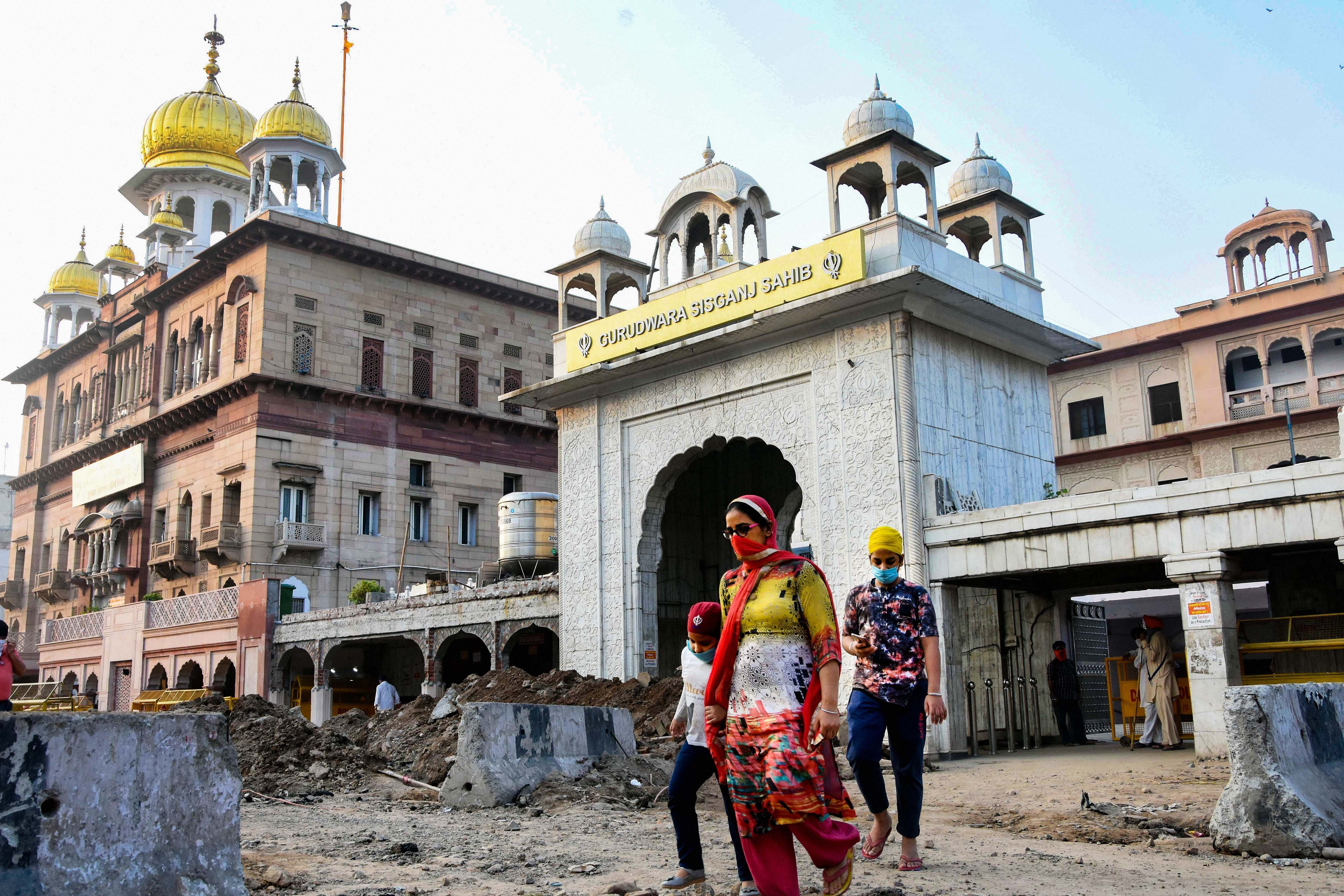 Devotees step out of Gurudwara Sis Ganj Sahib ji after offering prayers as the authorities permitted to open all religious places with certain restrictions, during the fifth phase of ongoing Covid-19 lockdown, in New Delhi, Monday, June 8, 2020.