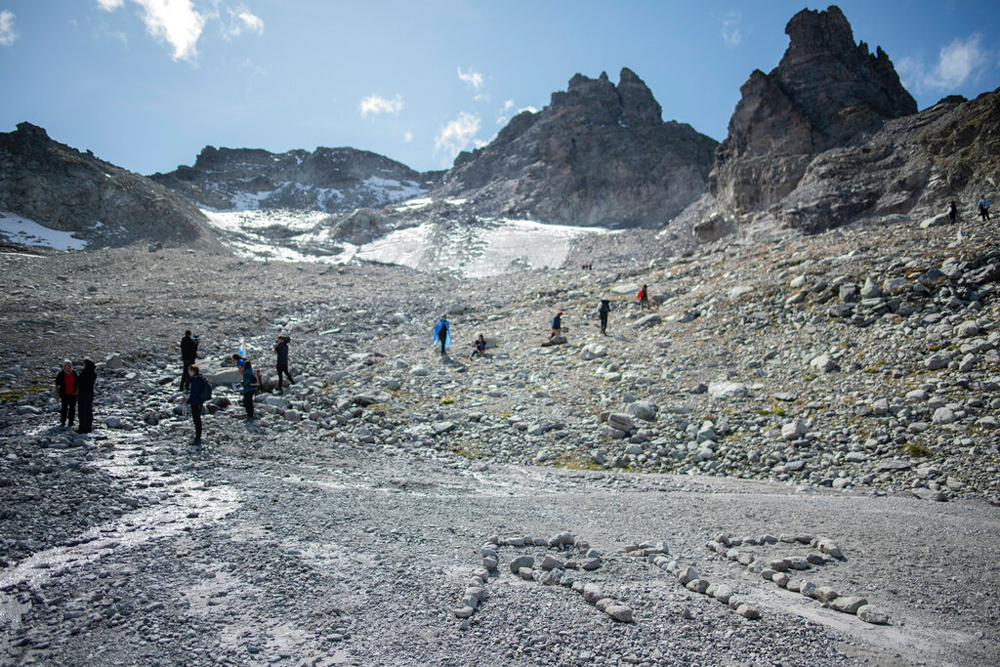 The letters RIP (rest in peace) written by activists with stones during a commemoration near the 'dying' glacier of Pizol mountain in Wangs, Switzerland, on Sunday
