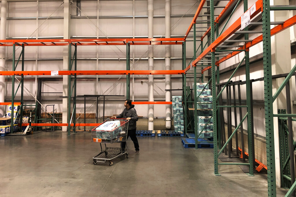A customer walks past mostly empty shelves that normally hold toilet paper and paper towels at a Costco store in Teterboro
