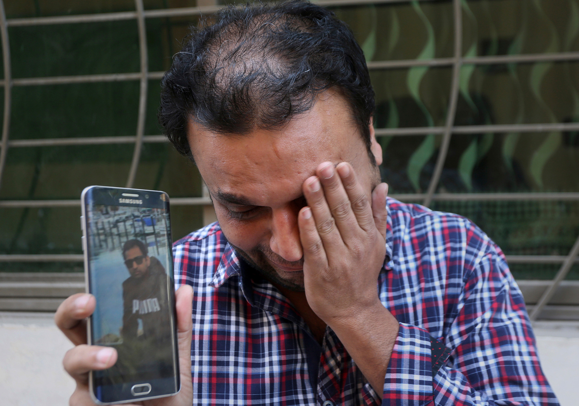 A relative weeps while holding up a picture of Sohail Shahid, a Pakistani citizen who was killed in Christchurch mosque shootings, on his cell phone outside his home in Lahore, Pakistan, on Sunday, March 17, 2019.