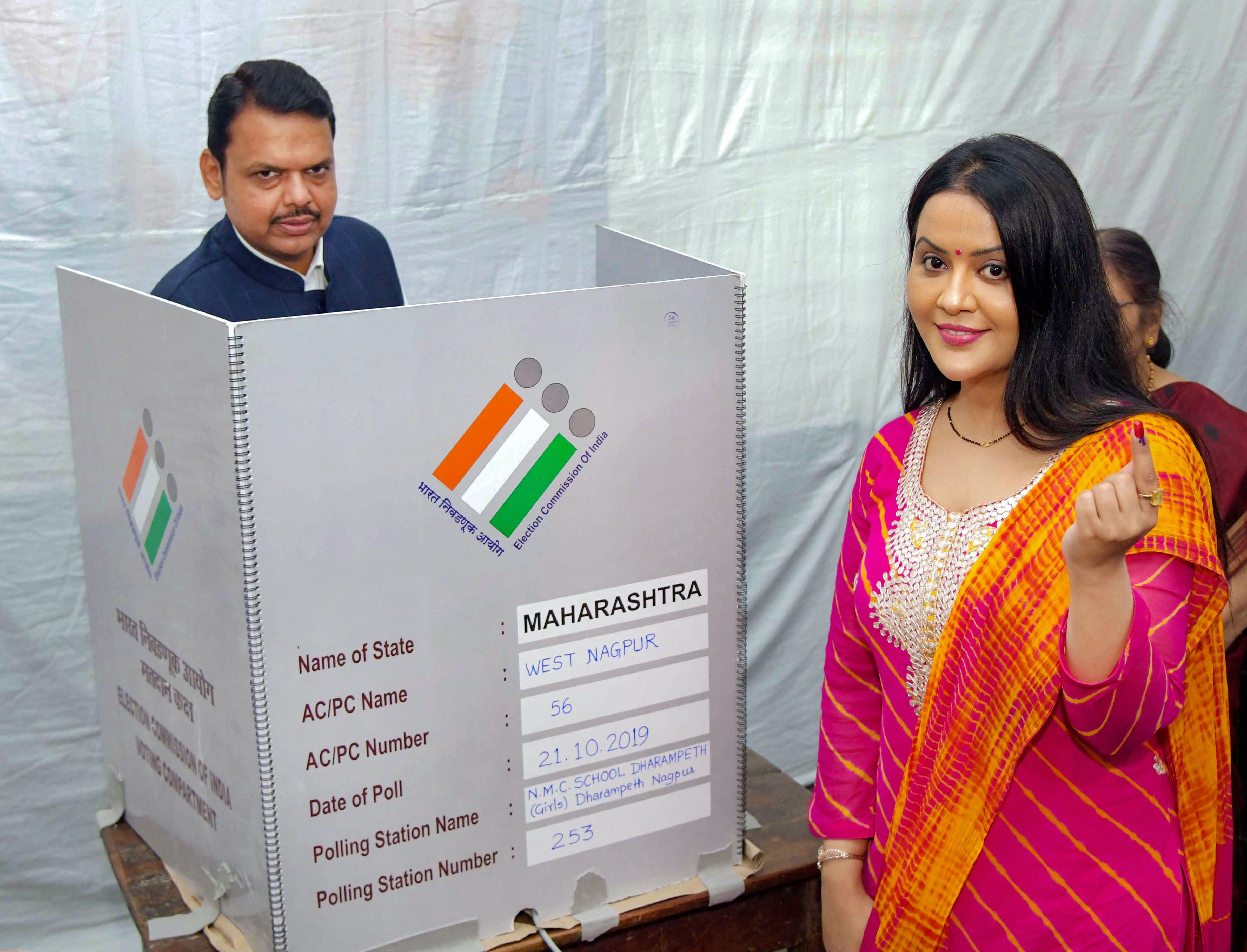 Maharashtra chief minister and Nagpur BJP candidate Devendra Fadnavis casts his vote while his wife Amruta shows her inked finger during the Maharashtra Assembly elections, in Nagpur, Monday, October 21, 2019