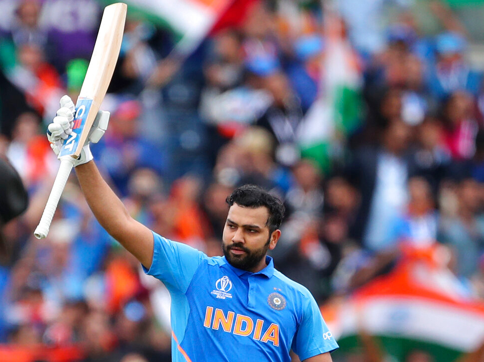 Rohit Sharma raises his bat to celebrate scoring a century during the Cricket World Cup match between India and Pakistan at Old Trafford in Manchester, England, Sunday, June 16, 2019.