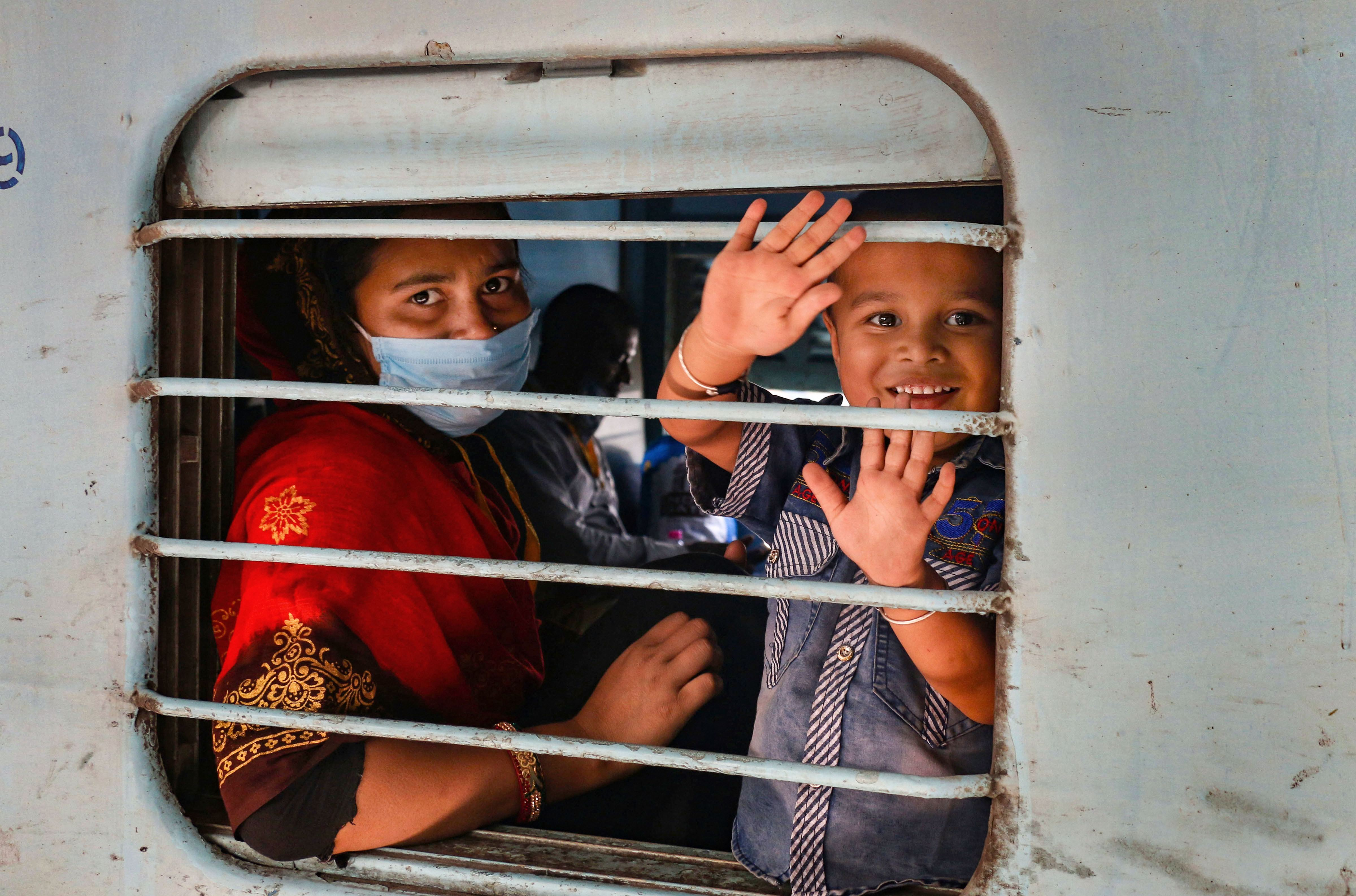 Migrant workers and pilgrims wave as they board a train to their native places in Ajmer on Monday.