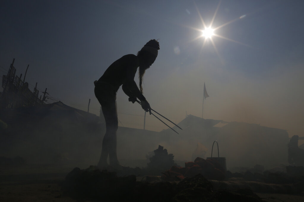 A Hindu holy man performs a ritual by burning dried cow dung cakes in earthen pots at Sangam, the confluence of the rivers Ganges, Yamuna, and mythical Saraswati, at the annual traditional fair of Magh Mela in Prayagraj