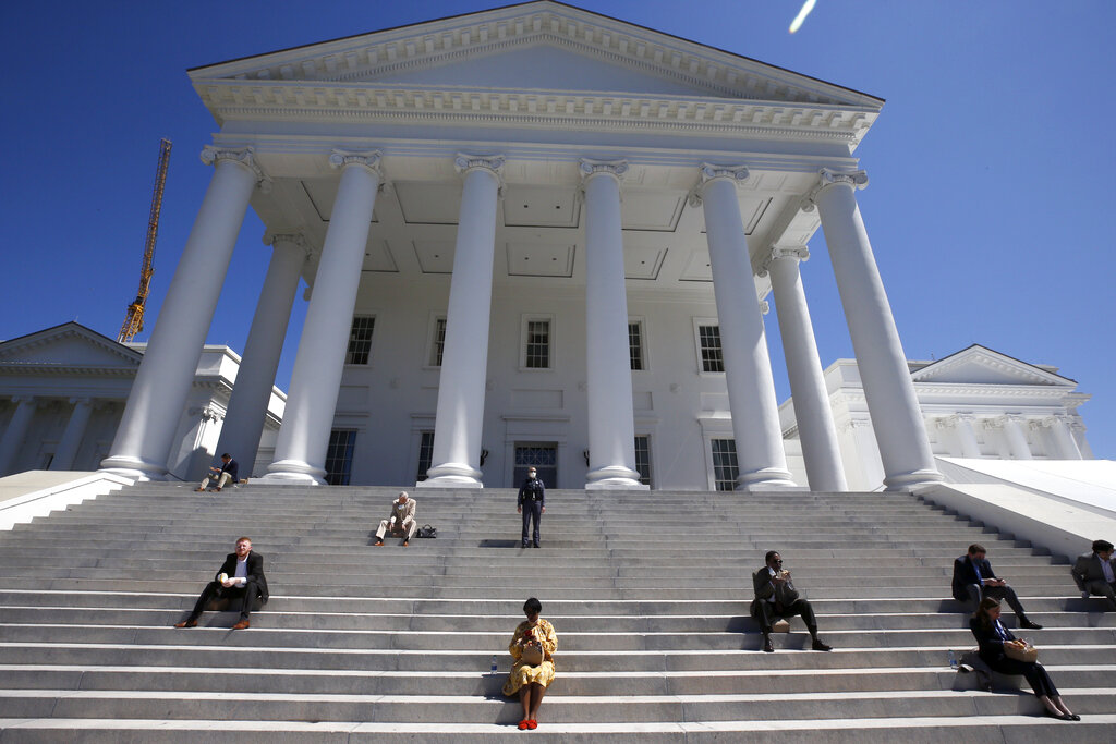 House of Delegates members eat boxed lunches on the steps of the Virginia State Capitol in Richmond, Va., before the veto session began Wednesday, April 22, 2020. The House members were meeting outside in a tent instead of the House Chamber in order to practice social distancing due to the coronavirus.