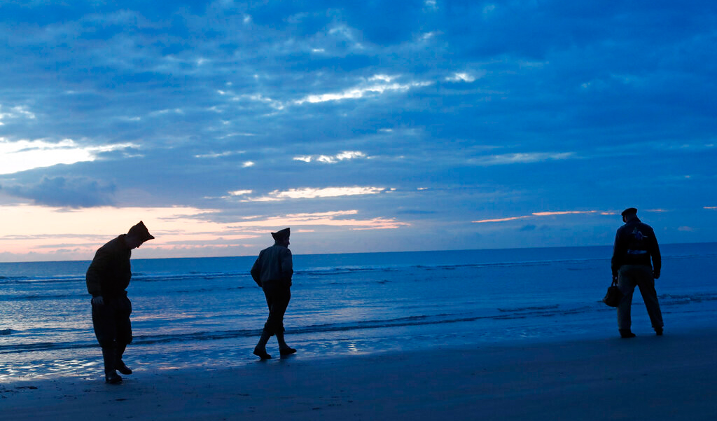 World War II re-enactors walk along Omaha Beach, in Normandy, France, at dawn on Thursday, June 6, 2019 during commemorations of the 75th anniversary of D-Day.