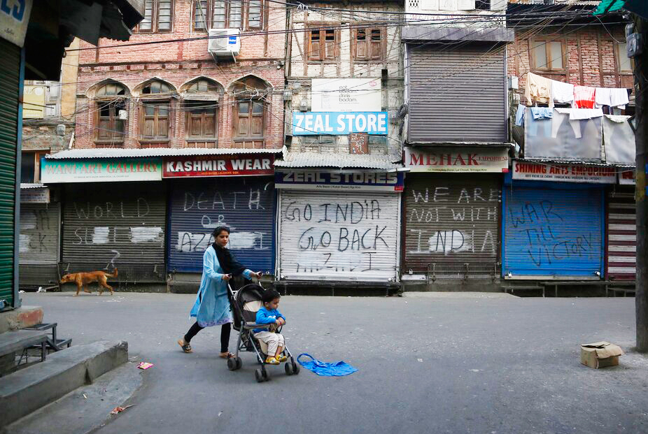 A Kashmiri woman pushes a child on a stroller past a closed market in Srinagar on Tuesday, September 24, 2019.