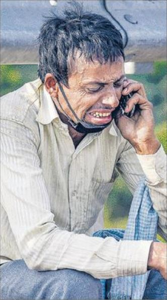 A migrant labourer breaks down as he speaks to a relative over his mobile phone in New Delhi on Monday.