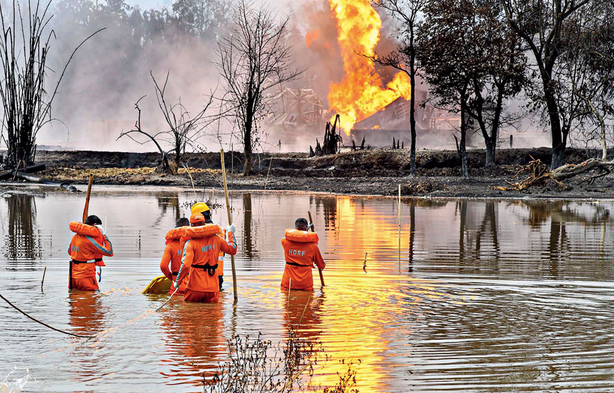 National Disaster Response Team personnel carry out search and rescue operations at Baghjan oilfield in Assam's Tinsukia district on Wednesday.