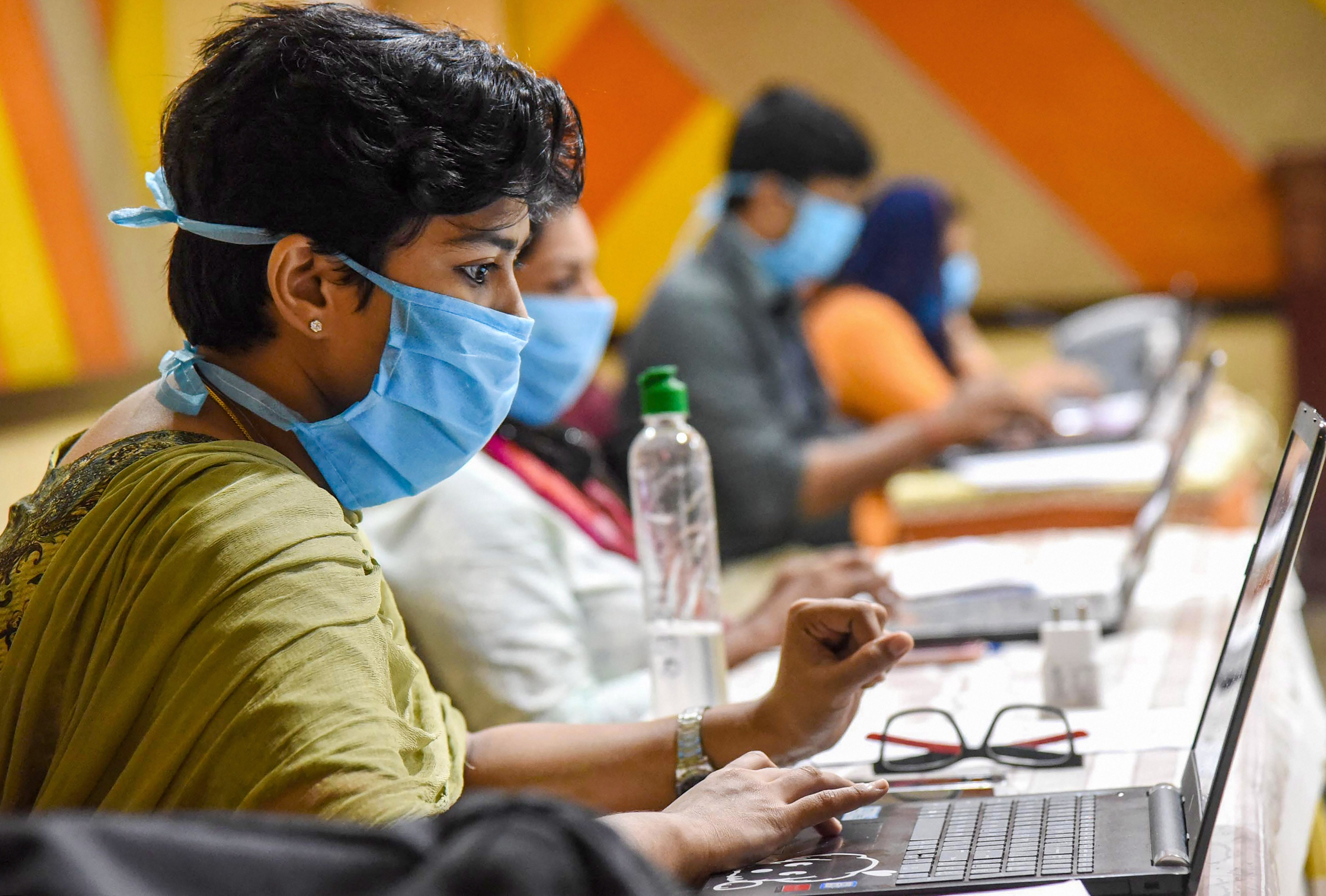 Employees of Health Tele Helpline center wearing face masks are seen working during a nationwide lockdown in the wake of coronavirus pandemic, at IMA house Ernakulam District in Kochi, Saturday, April 18, 2020.