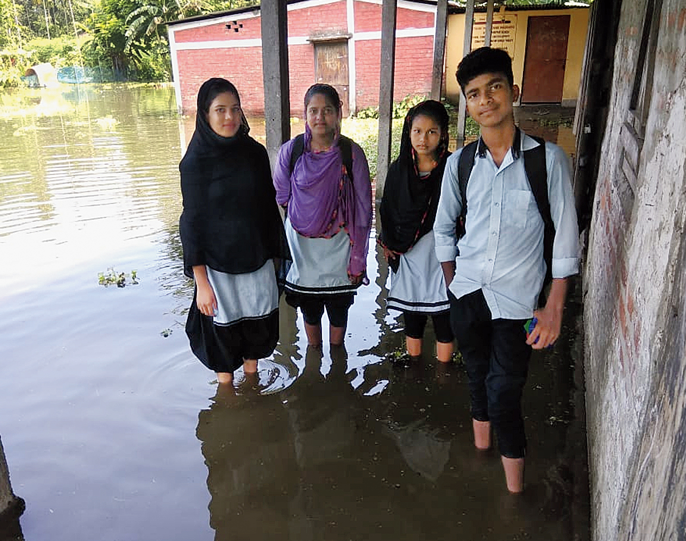 Students on a flooded school campus in Barpeta on Friday.