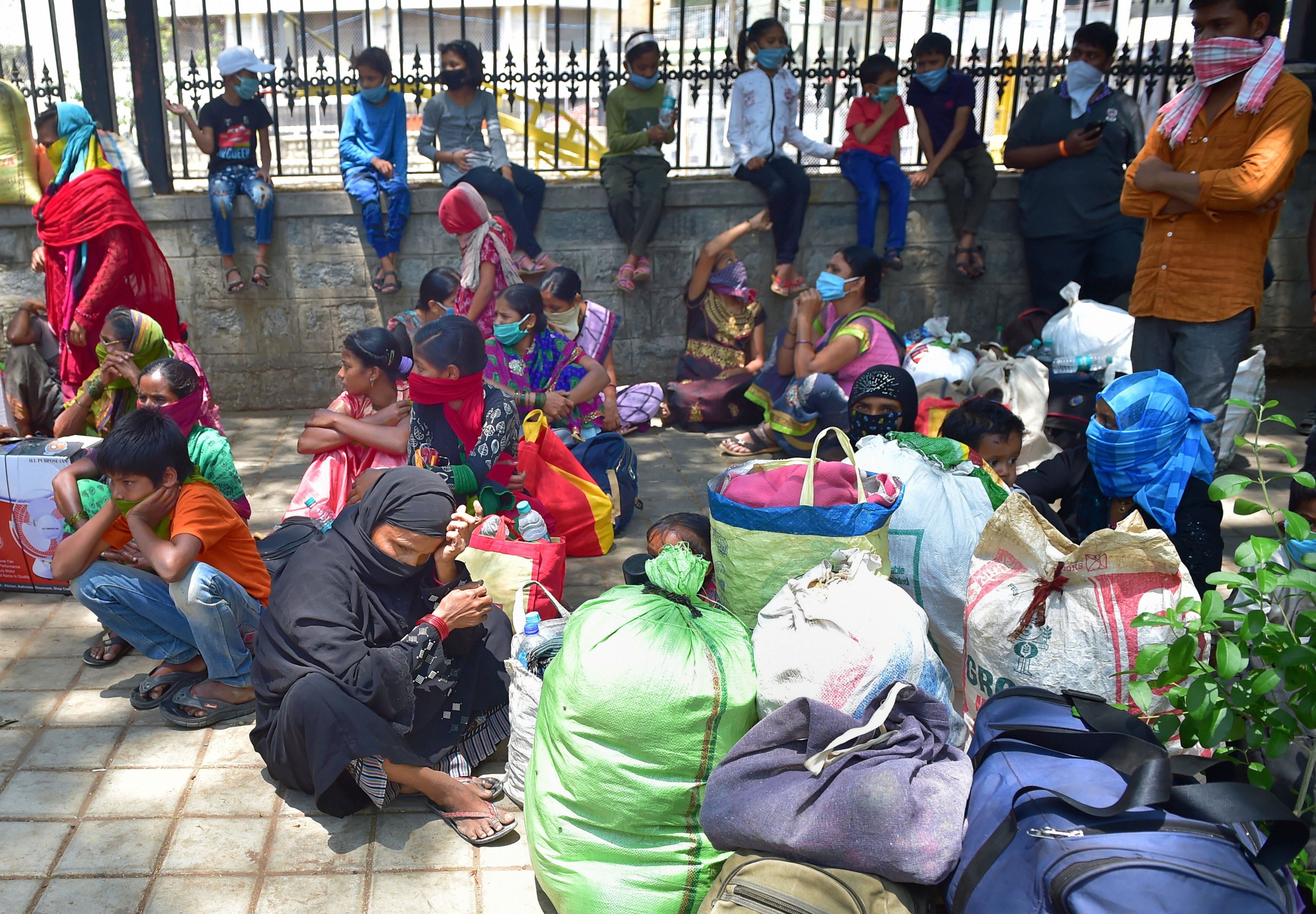 Migrant workers wait outside the District Collectors office for arrangements to return to their native places, amid ongoing Covid-19 lockdown in Bangalore