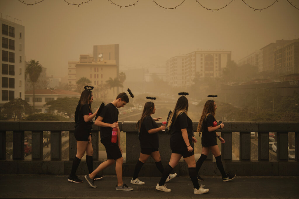 People in carnival dress walk across a bridge in a cloud of red dust in Santa Cruz de Tenerife, Spain. Flights leaving Tenerife have been affected after storms of red sand from Africa's Saharan desert hit the Canary Islands. Saturday's carnival was cancelled but Sunday's events are going ahead.