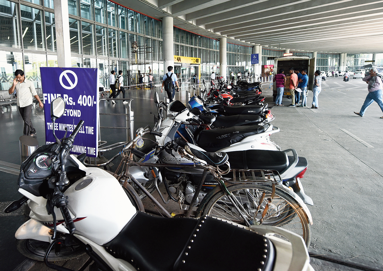 """Two-wheelers parked in front of the Calcutta airport's terminal building where a signboard reads """"Fine Rs 400 beyond three minutes dwell time  and seven minutes running time""""."""