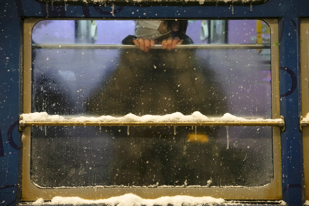 A commuter rides a tram during a snow storm in Sapporo, Hokkaido