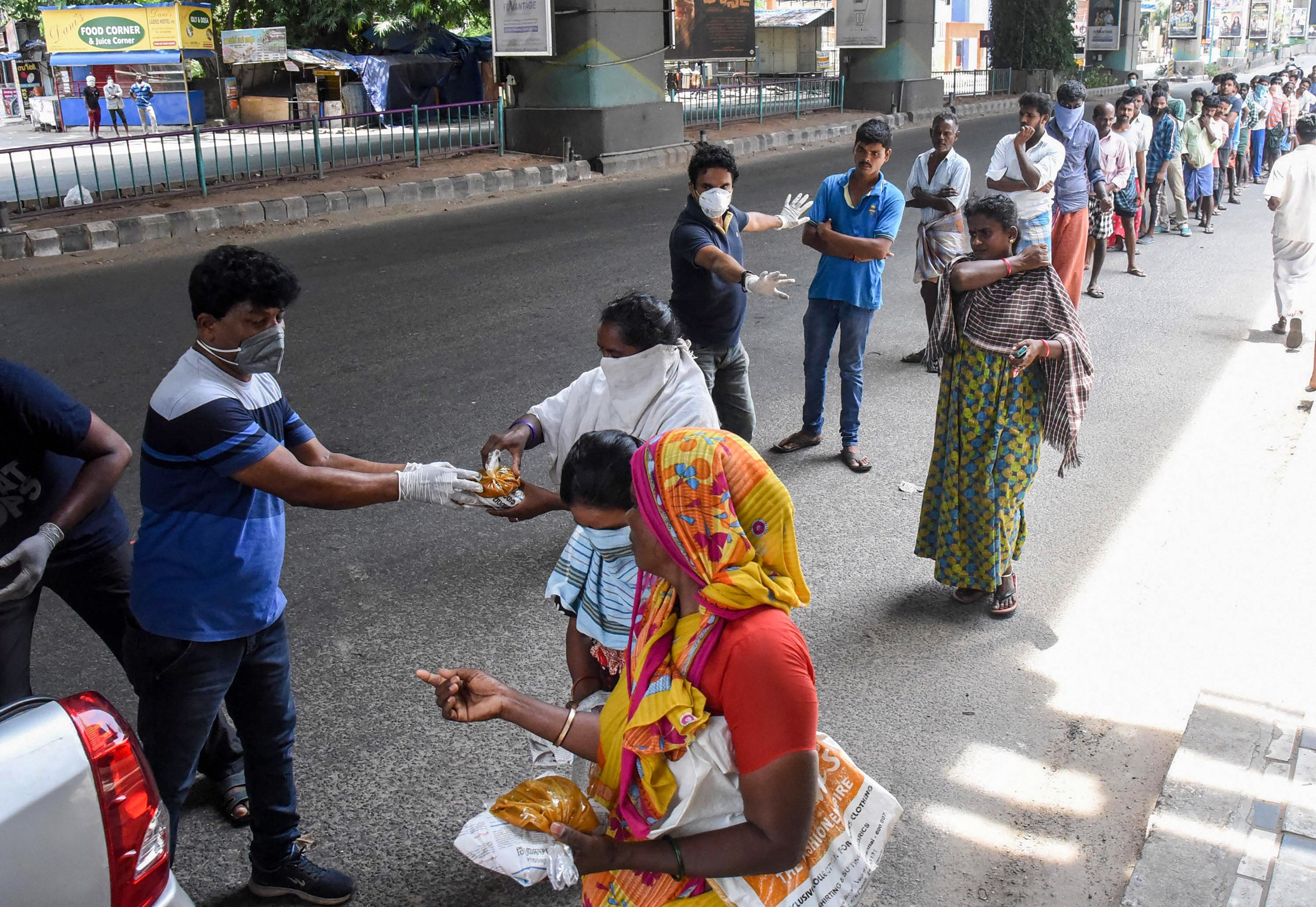 Social workers distribute food packets among the needy people during the nationwide lockdown imposed to contain the spread of coronavirus, in Kochi, Monday, April 6, 2020.