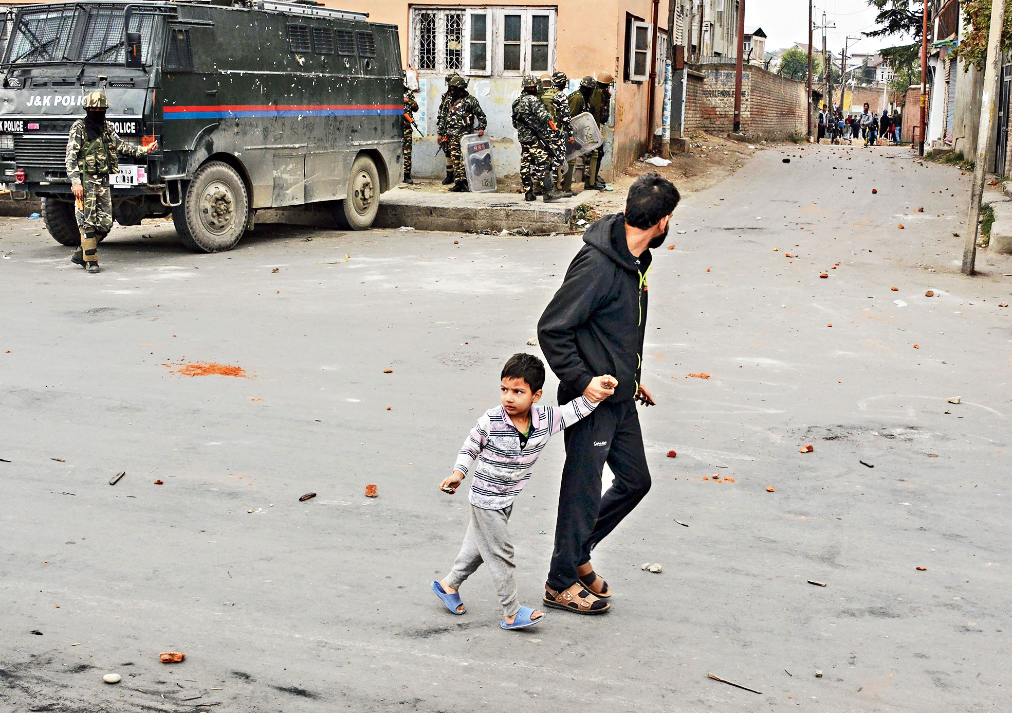 A man and a child run for cover during a clash near a polling station in Srinagar on Tuesday.