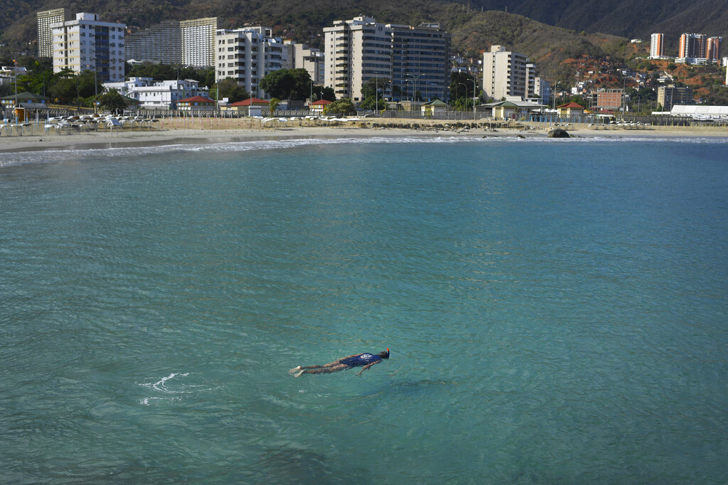 A man swims in the normally crowded popular beach Los Corales, in La Guaira, Venezuela, Saturday, March 21, 2020. Most people are staying home after nonessential activities were cancelled due to the COVID-19 pandemic.