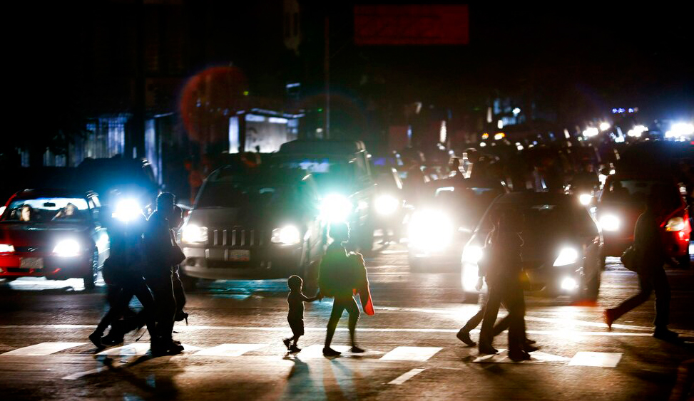 Residents cross a street in the dark after a power outage in Caracas, Venezuela on Thursday, March 7, 2019.