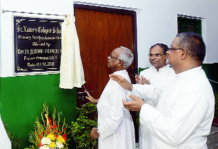 Father Jerome Francis unveils a plaque for the kindergarten section of St Xavier's Collegiate School on Monday as Father Benny Thomas (centre) and Father Dominic Savio look on.