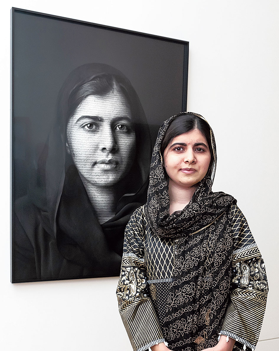 Malala Yousafzai with her portrait by Shirin Neshat at the National Portrait Gallery, London.