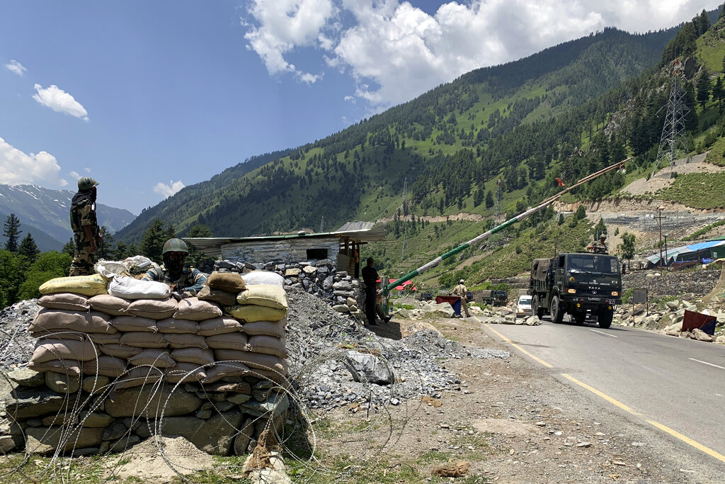 Indian paramilitary soldiers keep guard as Indian army convoy moves on the Srinagar- Ladakh highway at Gagangeer