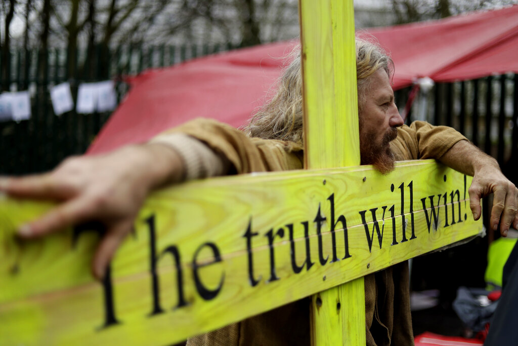 A supporter leans on a wooden cross which reads 'The truth will win' as he protests against the extradition of Wikileaks founder Julian Assange outside Belmarsh Magistrates Court in London, Monday, February 24, 2020. The U.S. government and WikiLeaks founder Julian Assange will face off Monday in a high-security London courthouse, a decade after WikiLeaks infuriated American officials by publishing a trove of classified military documents.
