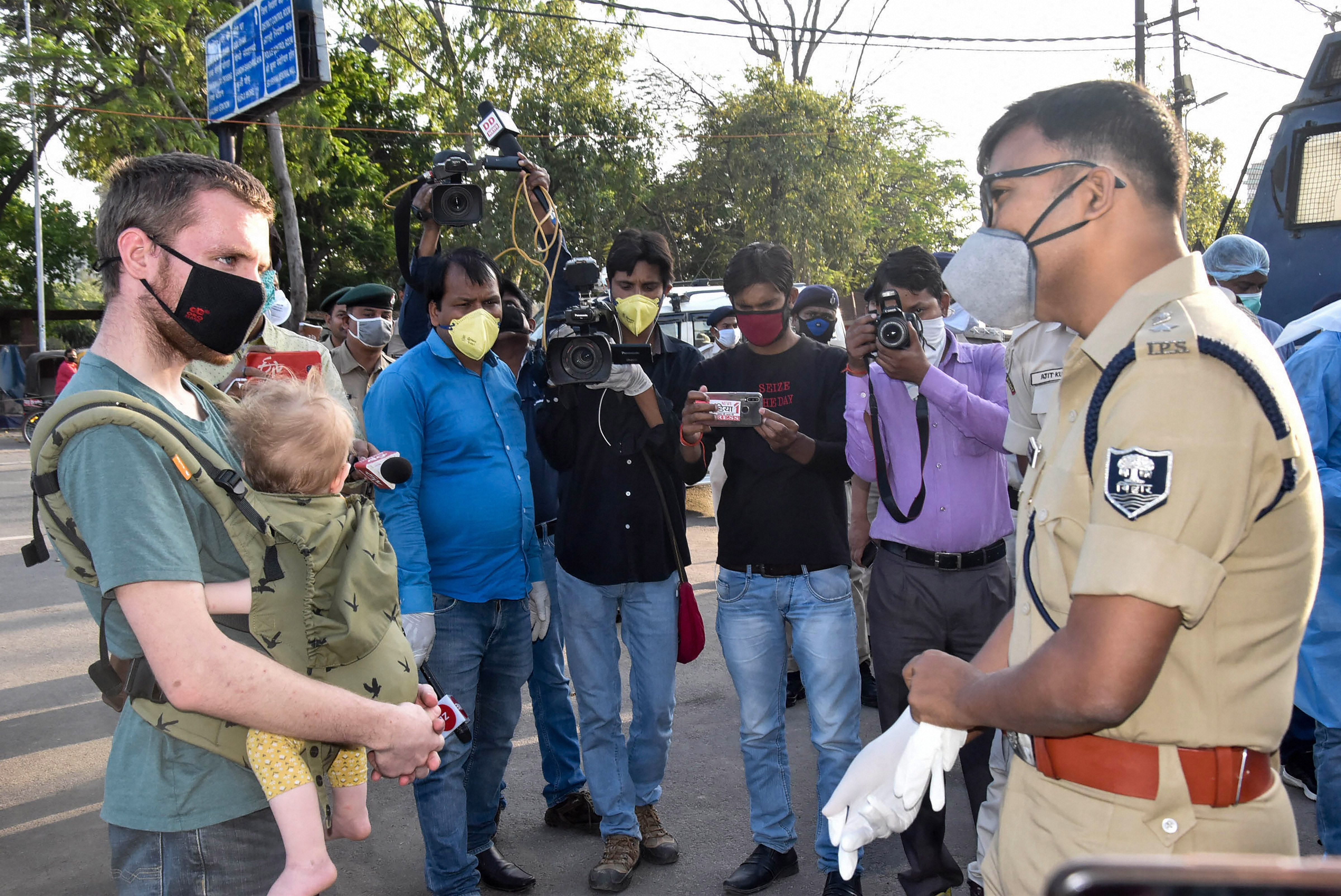 SSP Upendra Prasad Singh enquires from US tourists about their travel history during a nationwide lockdown in the wake of coronavirus outbreak, in Patna