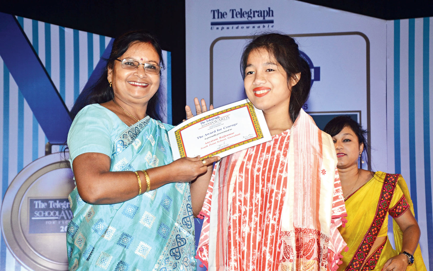 Anyatam Rajkumar's mother Niru Dutta Rajkumari (left) receives the award on his behalf.