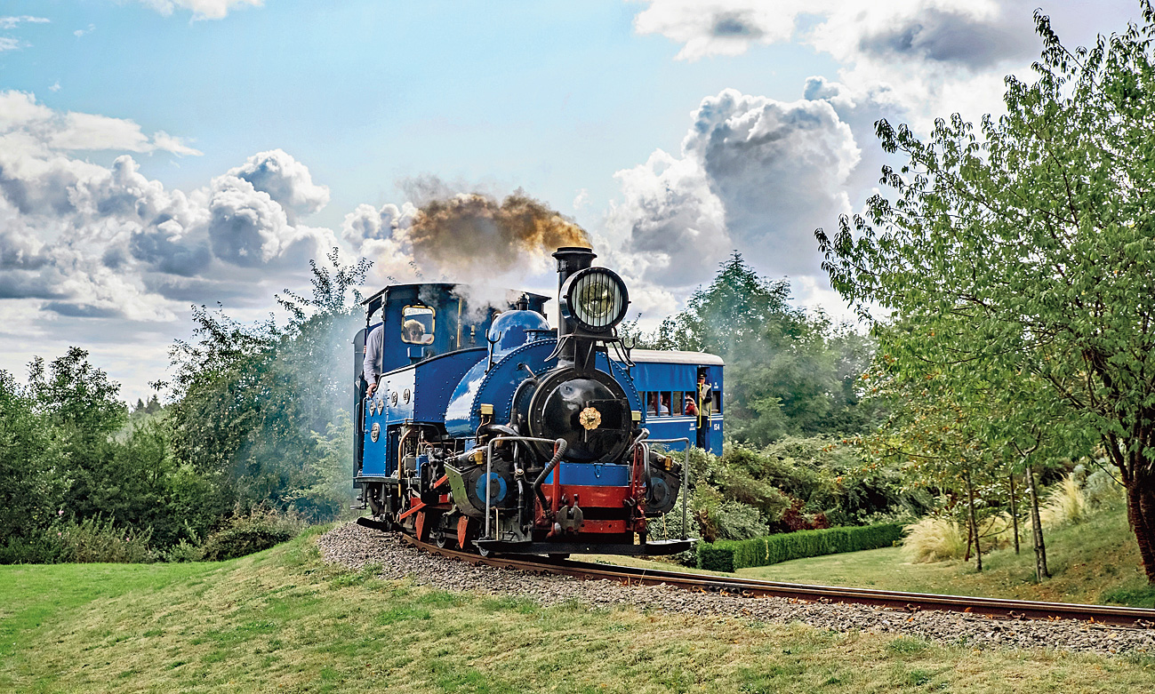 The DHR B class steam loco of the Beeches Light Railway hauls coaches at Steeple Aston in Oxfordshire, UK