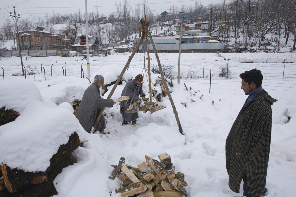 Kashmiri villagers load firewood buried under snow on a traditional weighing balance before selling it near Kangan village, north of Srinagar, Tuesday, Jan. 14, 2020.