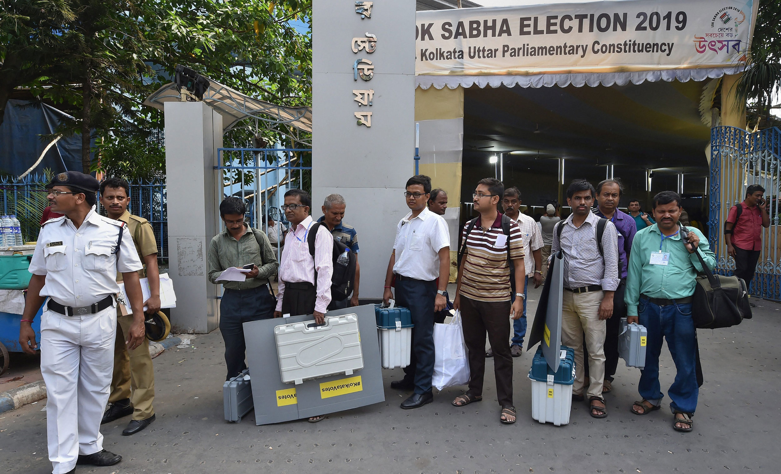 Election officials wait with EVMs, VVPAT machines and other equipments ahead of the seventh and last phase of Lok Sabha polls, in Calcutta, on May 18, 2019.