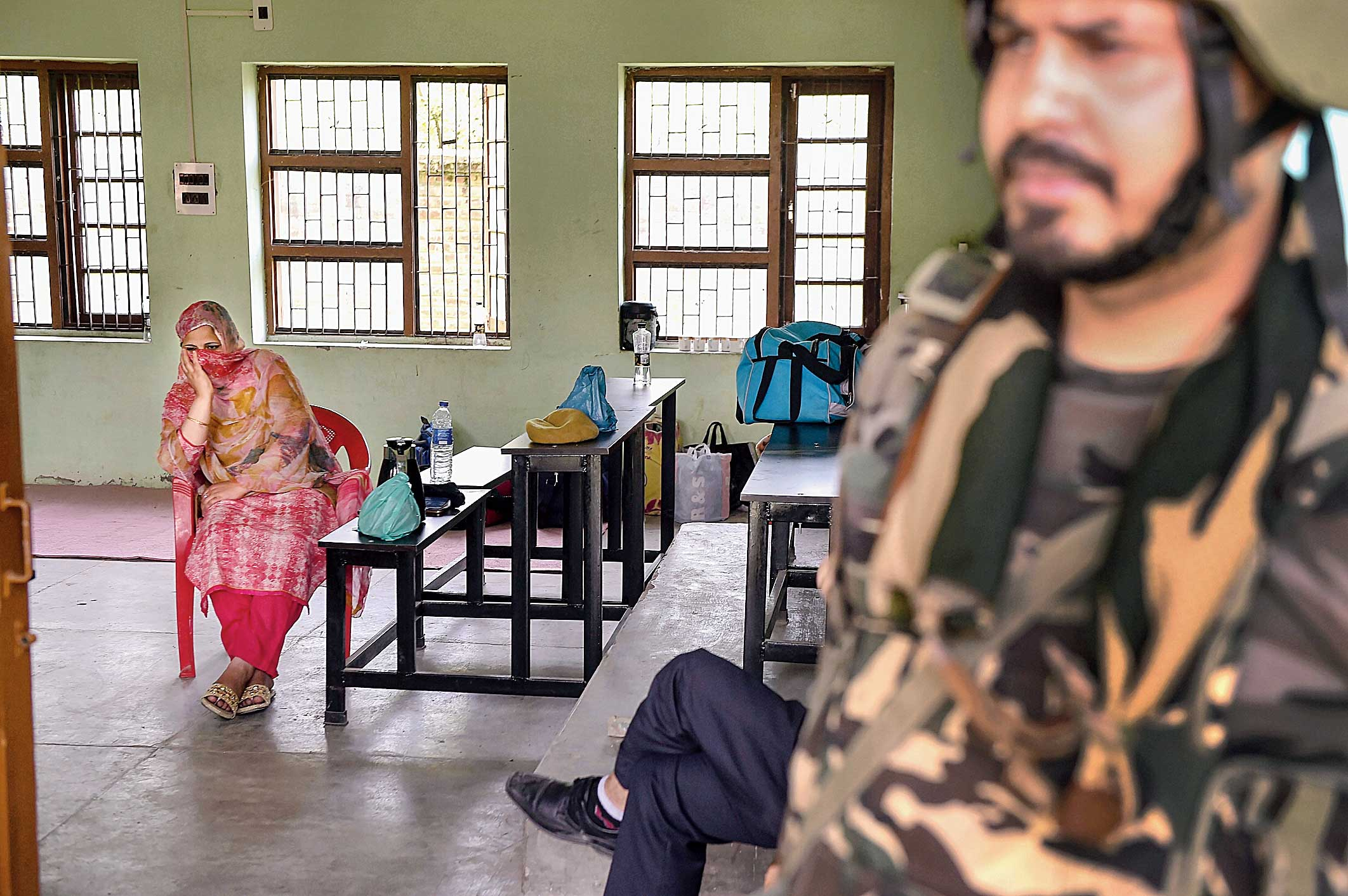 A security person stands guard as an election official waits for voters at a polling station in Anantnag on Tuesday.