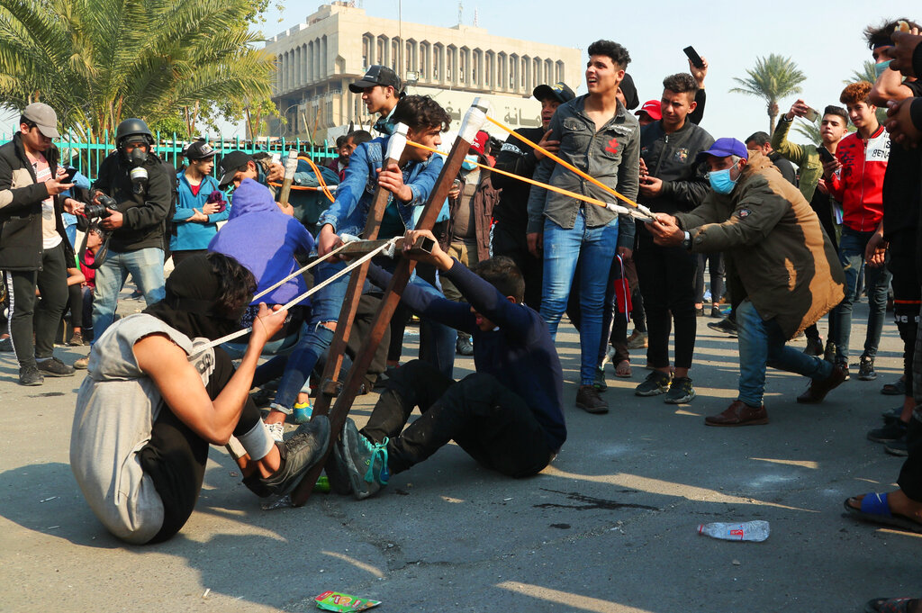 Anti-government protesters use a slingshot to fire a stone at security forces during clashes in Baghdad, Iraq, on Thursday