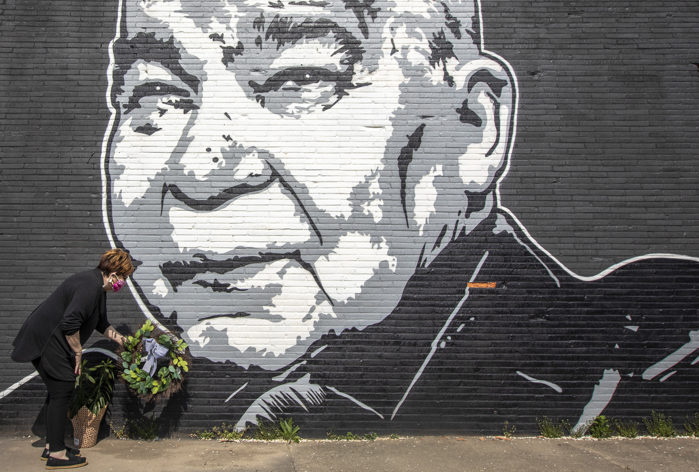 Maribeth Schmitt, of Lexington, Ky., places a wreath below a mural of singer John Prine, painted by Graham Allen of SquarePegs Studio and Design