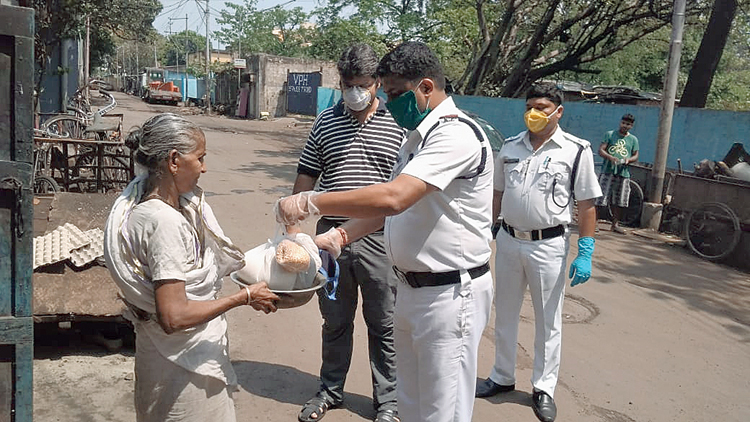 A police officer hands over essential items to a woman in Sinthee