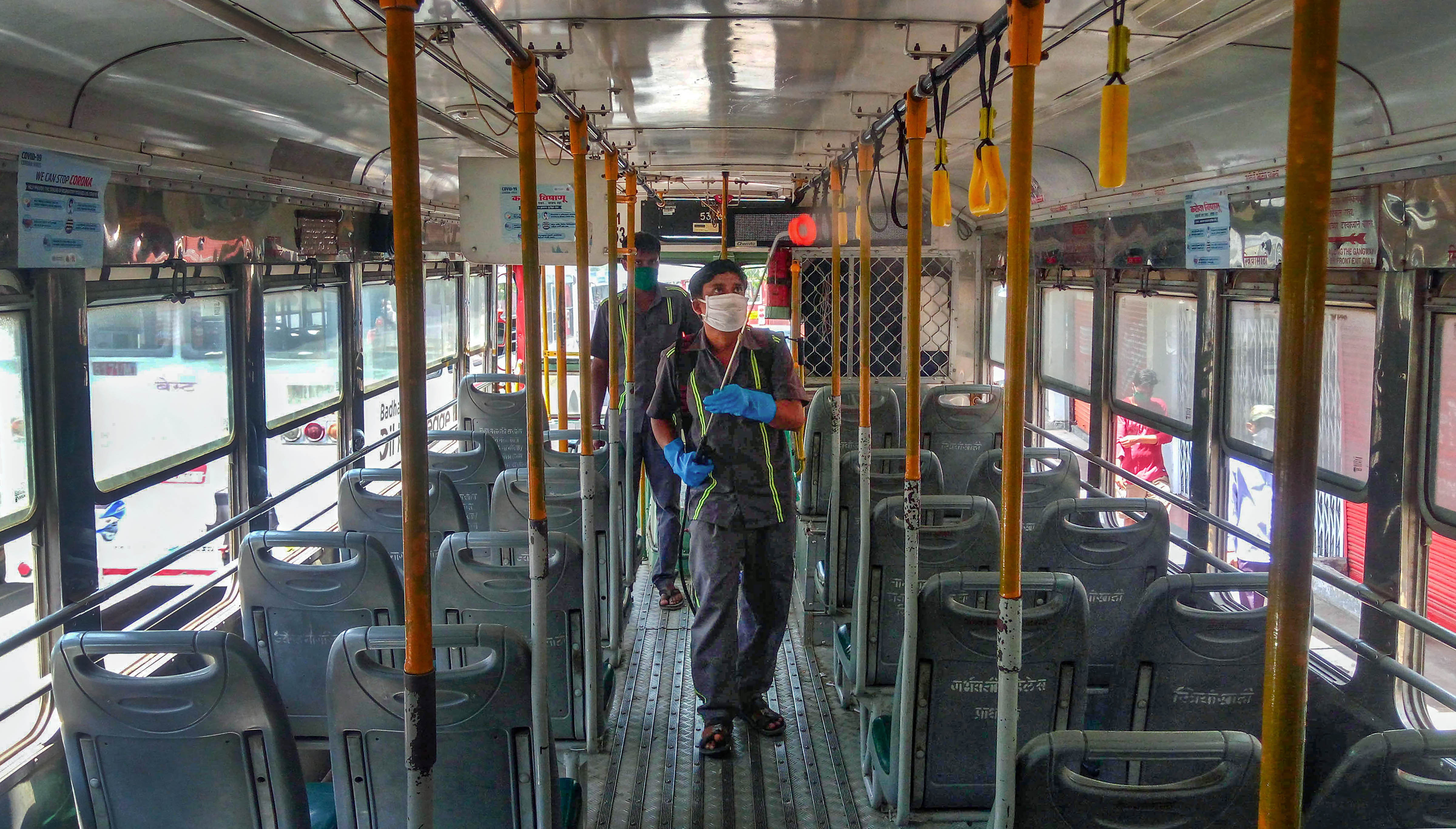 Municipal Corporation (BMC) worker sprays disinfectant inside a Brihanmumbai Electricity Supply and Transport (BEST) bus, during the nationwide lockdown in the wake of the coronavirus pandemic, at Borivali in Mumbai, Wednesday, April 8, 2020.