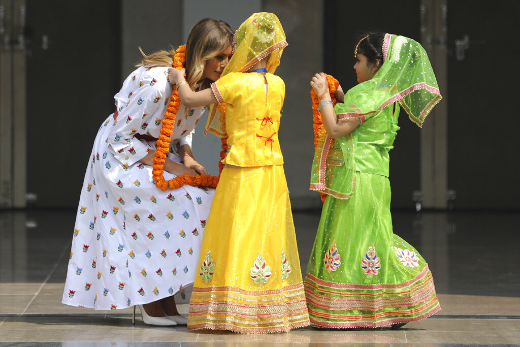 US first lady Melania Trump is garlanded by two children at Sarvodaya Co-Educational Senior Secondary School in New Delhi