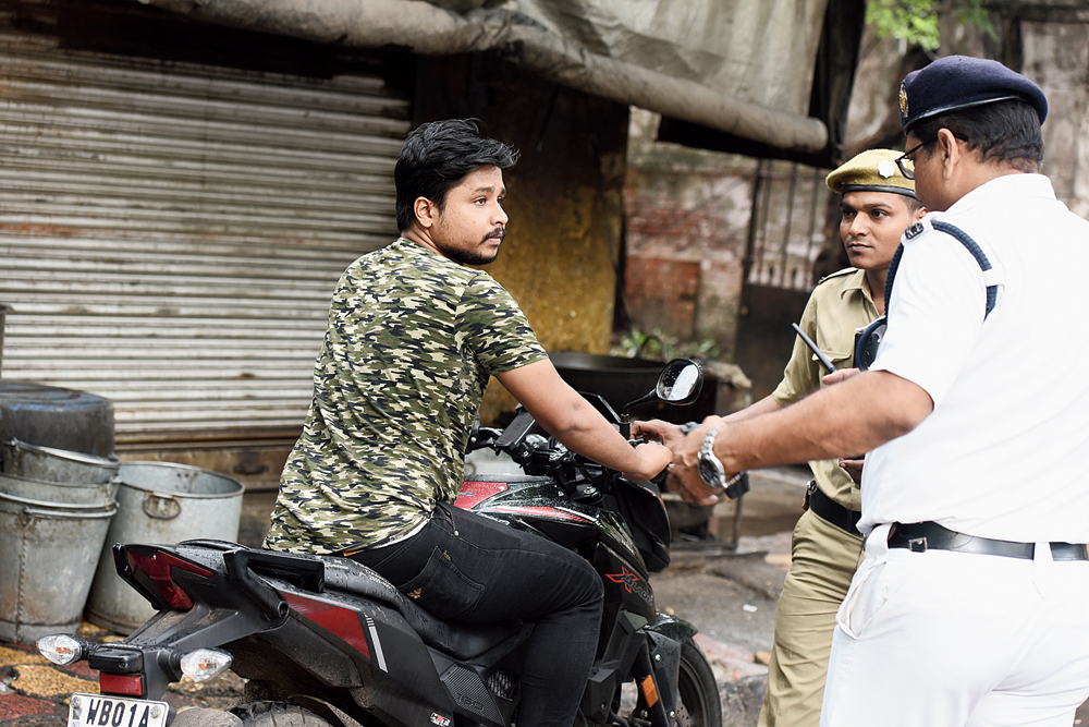A traffic policeman and a homeguard intercept a biker without a helmet at the crossing of Syed Amir Ali Avenue and Mayfair Road on Tuesday afternoon. The cops fined the biker.