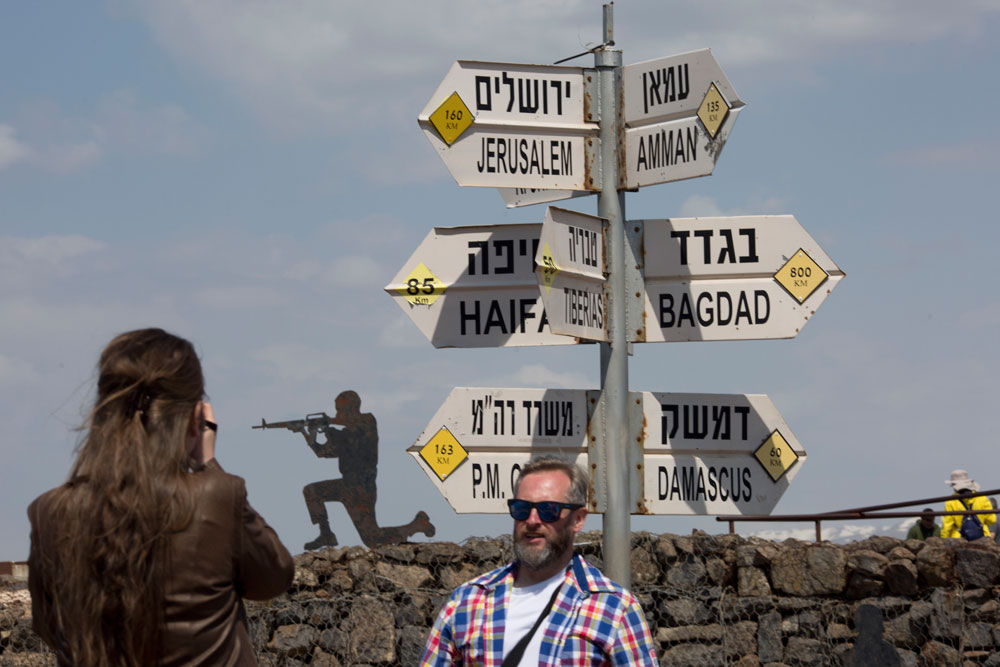 Tourists pose for photograph next to a mock road sign for Damascus, the capital of Syria, and other capitals and cities and a cutout of a soldier at Golan Heights near the border with Syria on Friday