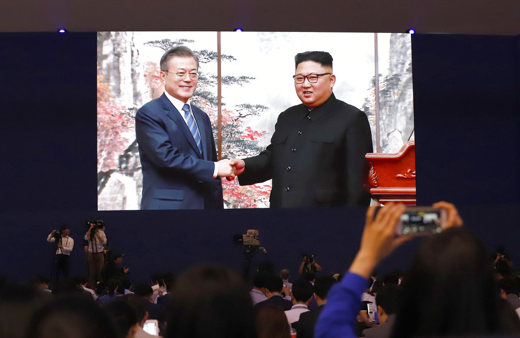 Members of media and volunteers watch a huge screen showing Moon Jae-in (left) shake hands with Kim Jong-un after their joint press conference in Pyongyang.