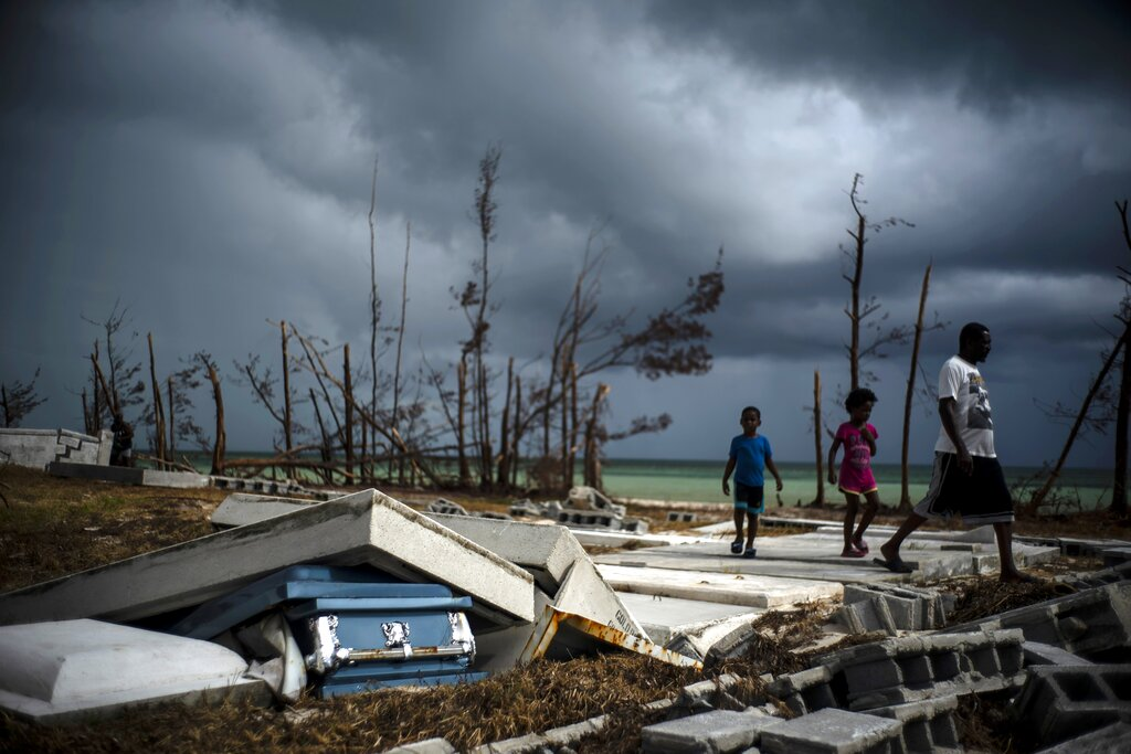 People walk next to a shattered and water-filled coffin, which lays exposed to the elements, in the aftermath of Hurricane Dorian, at the cemetery in Mclean's Town, Bahamas, Friday, September 13, 2019.