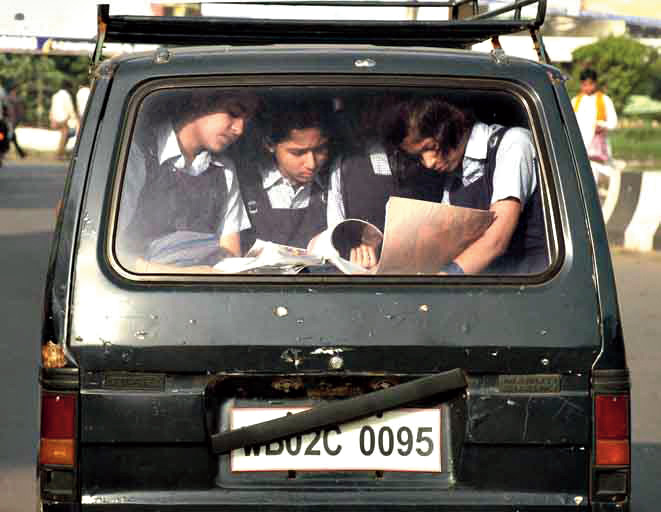 Students browse through text books in a pool car on their way to school to write an exam