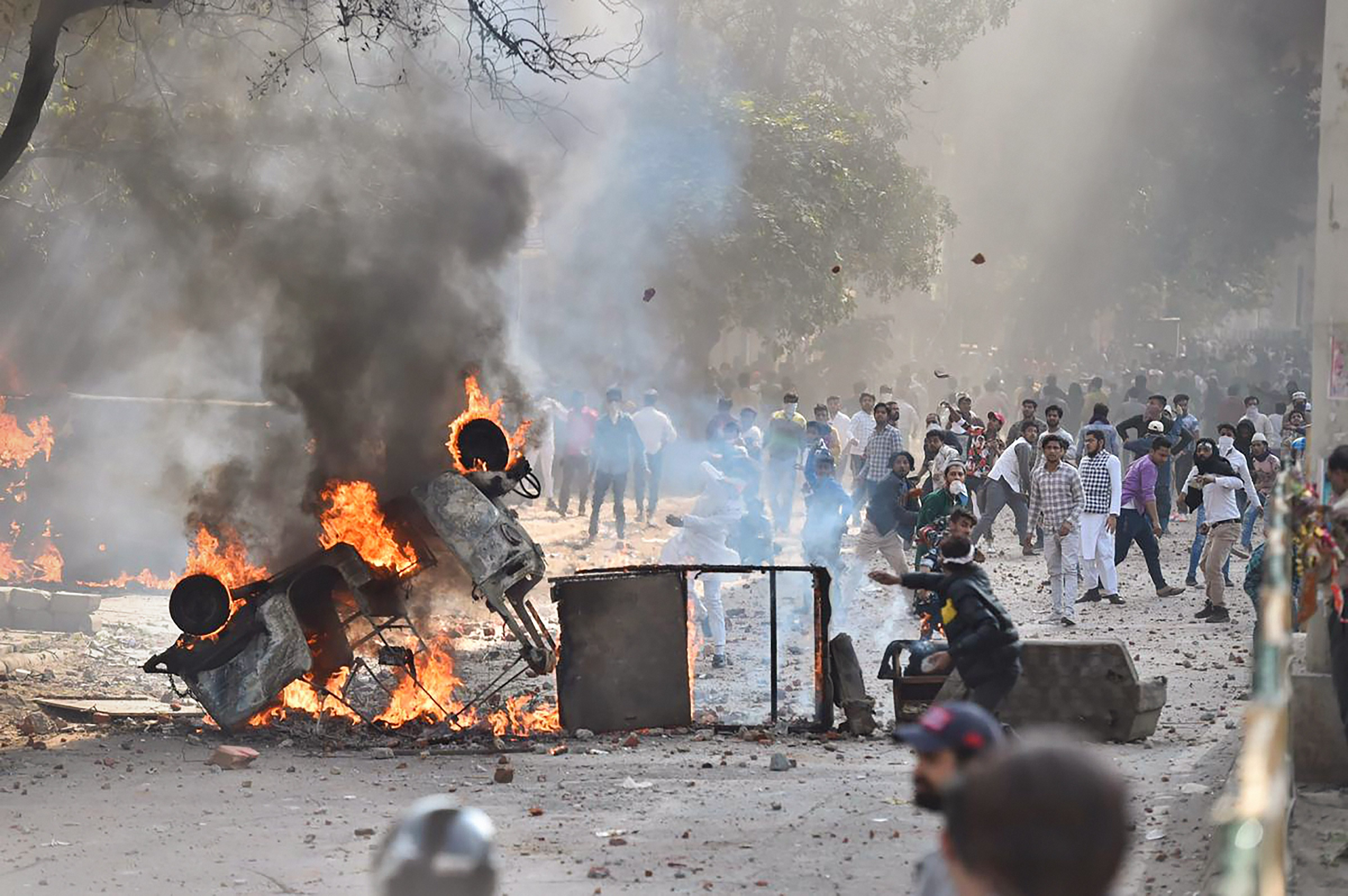 Vehicles set ablaze as protesters throw brick-bats during clashes between a group of anti-CAA protestors and supporters of the Citizenship (Amendment) Act, at Jafrabad in northeast Delhi, Monday, February 24, 2020