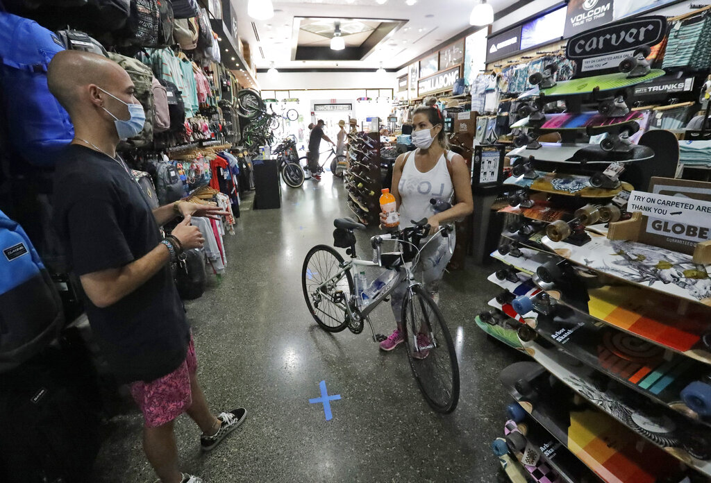 Guillermo Ley, left, an employee at Fritz's Skate Bike & Surf store on Miami Beach, Florida's famed Lincoln Road, attends to Michelle DeLeon, Wednesday, May 20, 2020.